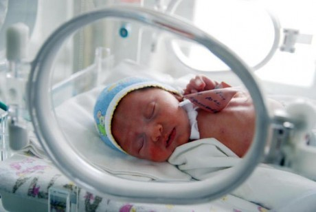 Ребенок в инкубаторе для интенсивного выхаживания новорожденных с малым весом
